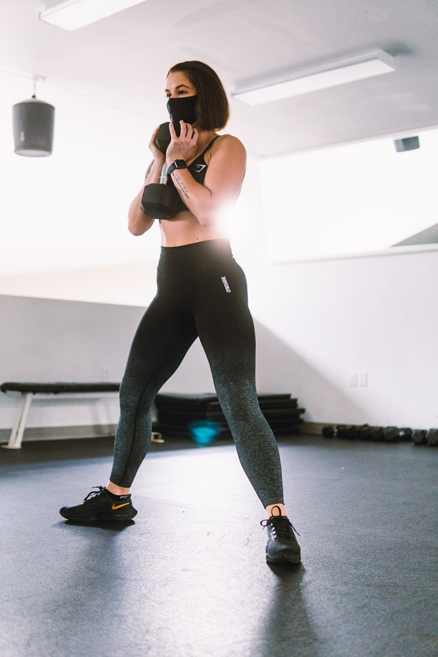 Woman working out at Reno health clubs in mask during covid-19